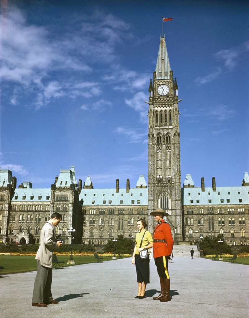 A_member_of_the_RCMP_poses_in_front_of_the_Parliament_Buildings_for_snapshooting_tourists._Ottawa,_Ontario,_Canada